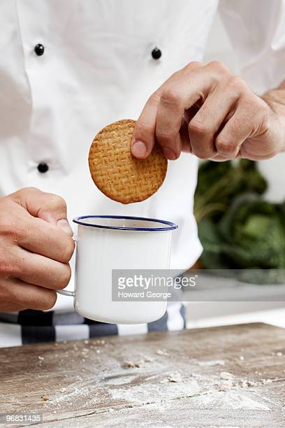 Chef dunking biscuit into mug of tea