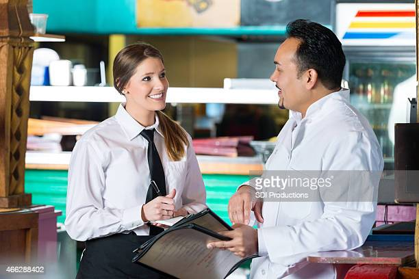 Chef explaining daily specials in menu to restaurant waitress
