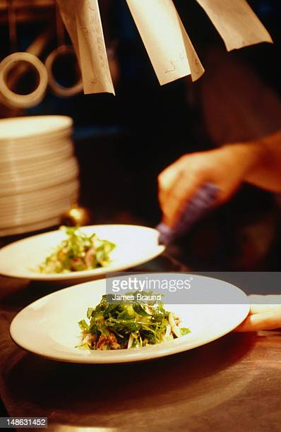 A chef finishes off the preparation of meals at one of Melbourne's premier restaurants.