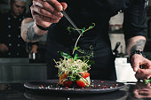 Chef finishing healthy salad on a black plate with tweezers. almost ready to serve it on a table
