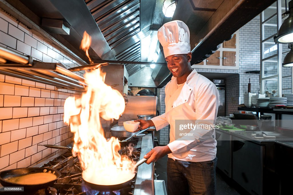 Chef flaming food at a restaurant : Stock Photo
