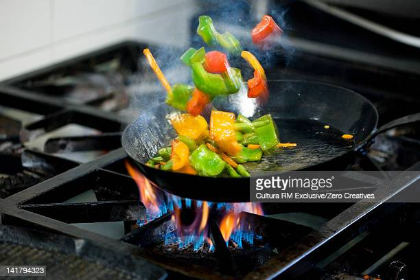Chef frying vegetables in kitchen