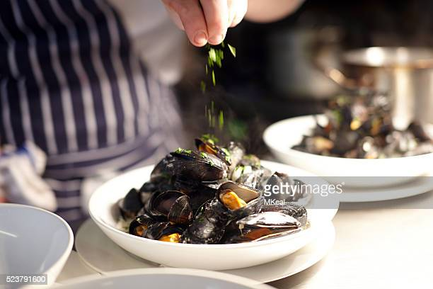 Chef garnishing a bowl of freshly cooked mussels with parsley