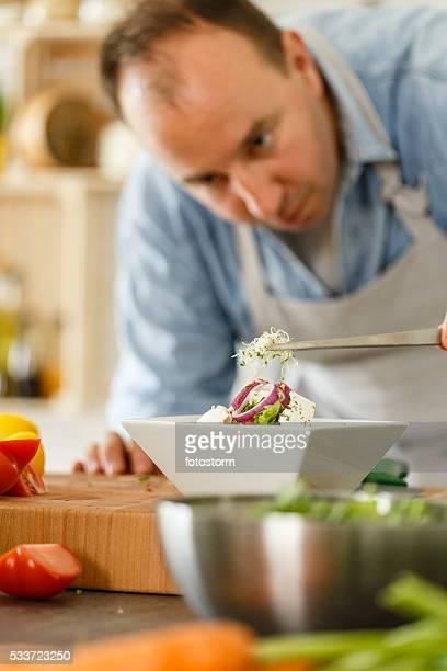 Chef garnishing gourmet food in kitchen