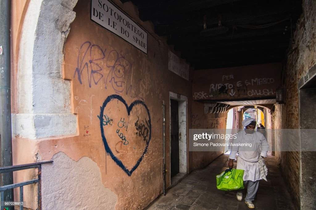 A chef goes to a storage room in the Sotoportego De Le Do Spade, where there are graffiti and tags on the walls, through San Polo district, on July 12, 2018 in Venice, Italy. The plague of graffiti and tags on the walls of the palaces of Venice continues with new writing across the doors, windows and the plaster of shops, banks, historic buildings, ruining and attacking the priceless architectural heritage of the lagoon. Venice has been living with this problem for years, but it has not reached a resolution until today.