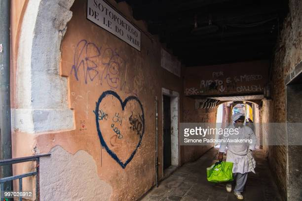 A chef goes to a storage room in the Sotoportego De Le Do Spade where there are graffiti and tags on the walls through San Polo district on July 12...
