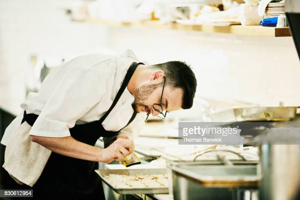 Chef grating cheese on freshly baked crackers in restaurant kitchen