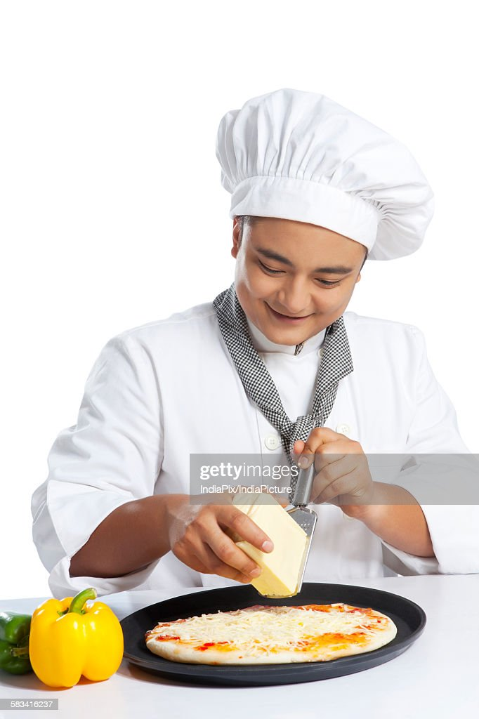 Chef grating cheese on pizza : Stock Photo
