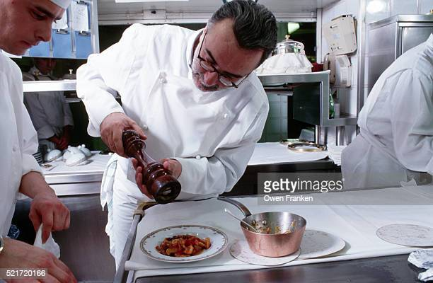 Chef Grinding Pepper Over a Dish of Food