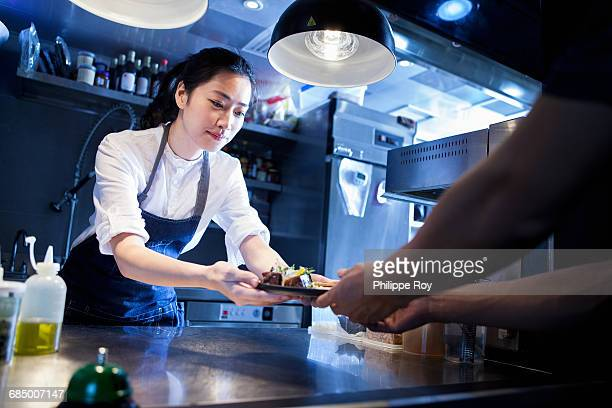 Chef handing prepared meal to waiter