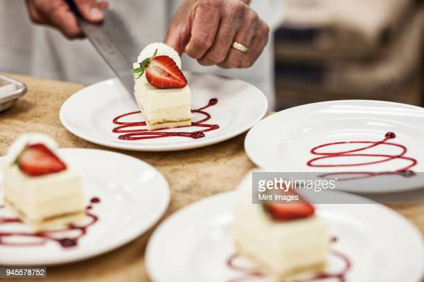 Chef hands placing a layered desert on a plate, presentation of a sweet dish.