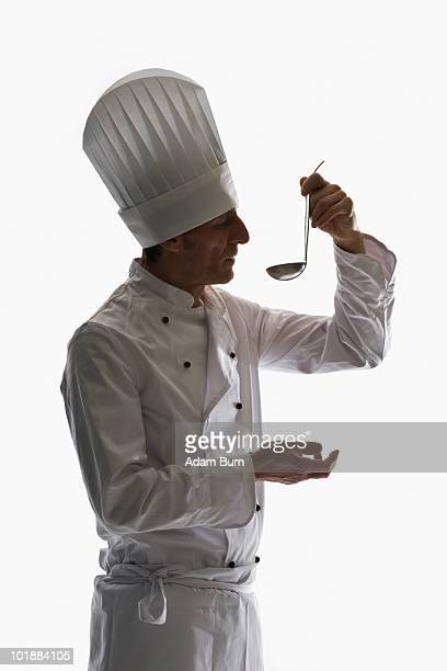 a chef holding a ladle up to his mouth, portrait - ladle stock photos and pictures