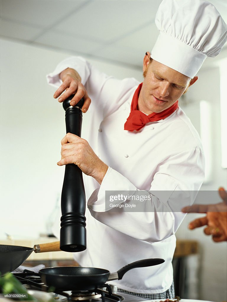 Chef Holding A Pepper Mill In The Kitchen Stock Photo | Getty Images