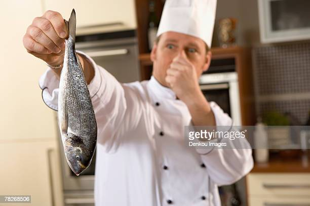 A chef holding a smelly fish