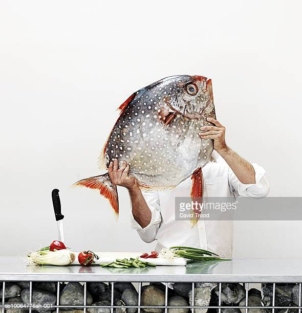 Chef holding big fish in commercial kitchen, obscured face, studio shot