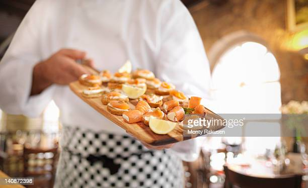 chef holding board of scottish smoked salmon and cream cheese canapes - オトレイ ストックフォトと画像