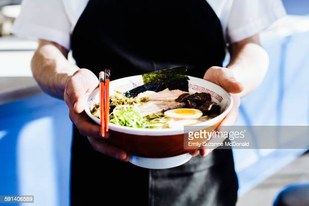 Chef holding bowl of ramen in restaurant