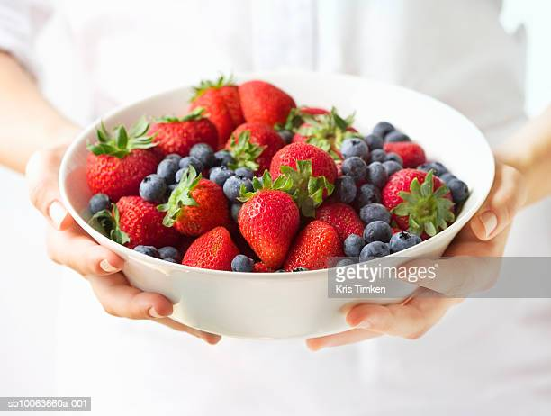Chef holding bowl of strawberries and blueberries, mid section