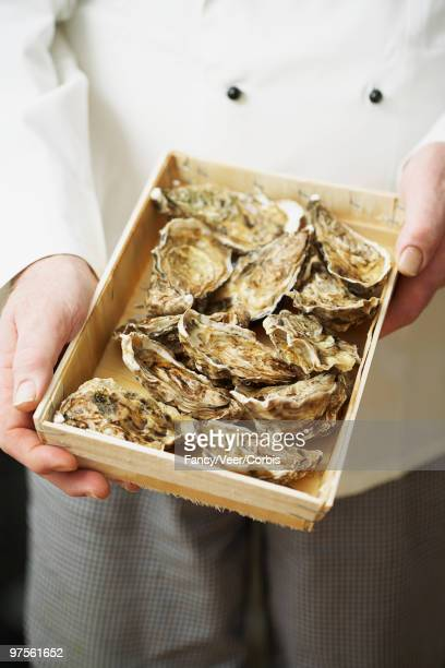 Chef holding box of oysters