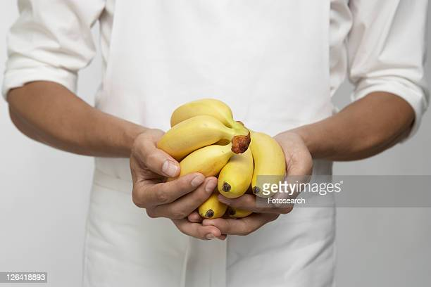chef holding bunches of bananas (mid section) - 束 ストックフォトと画像