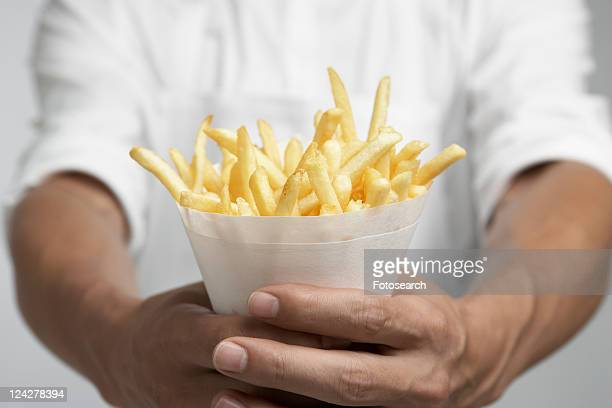 Chef holding french fries (mid section)