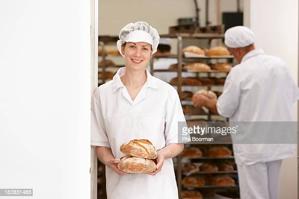 Chef holding loaves of bread in kitchen