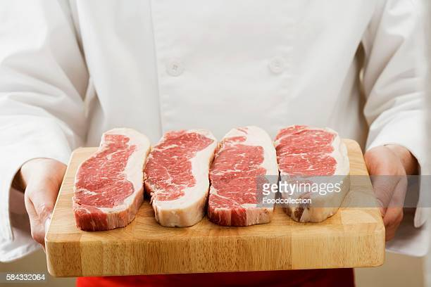 Chef holding sirloin steaks on chopping board