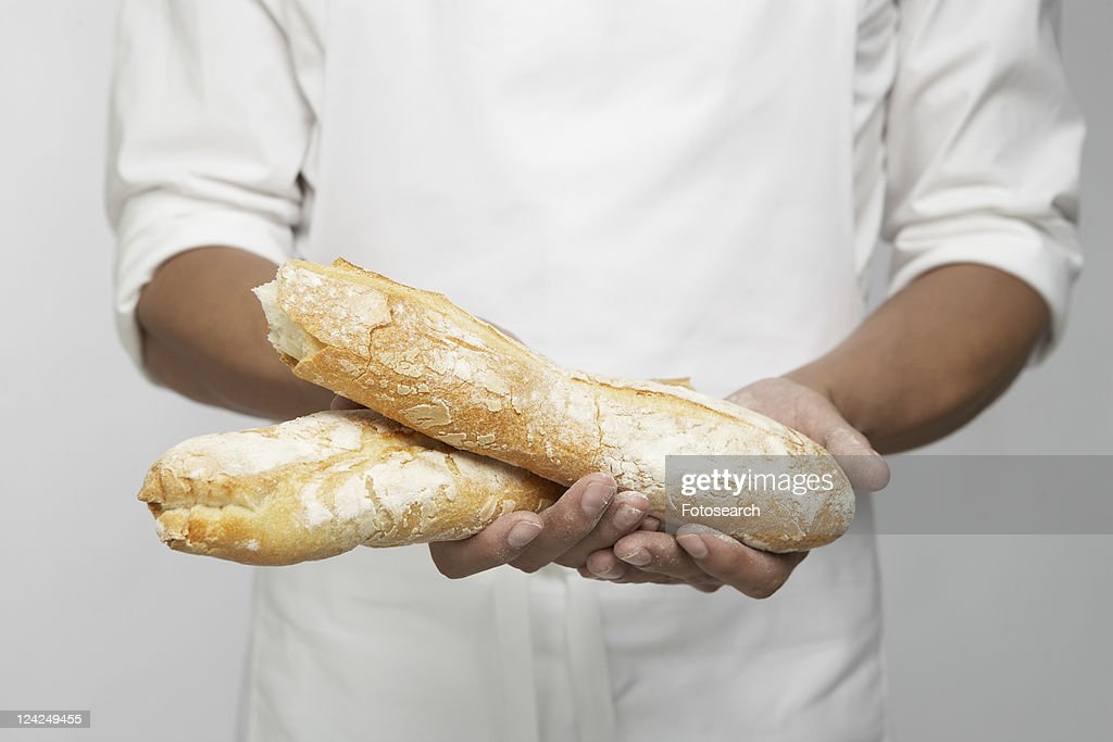 Chef holding two pieces of baguette (mid section) : Photo