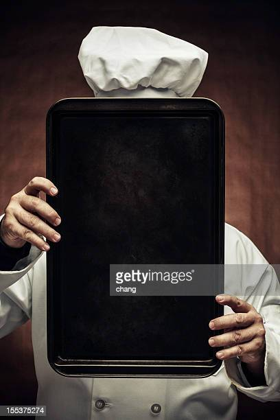 A chef holding up a baking tin