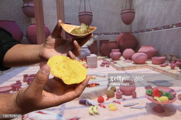 A chef holds Indus valley food with a backdrop of the ancient kitchen on February 20 2020 in New Delhi India What did humans eat 5000 years ago in...