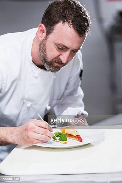 Küchenchef in restaurant Plattierung Speisen
