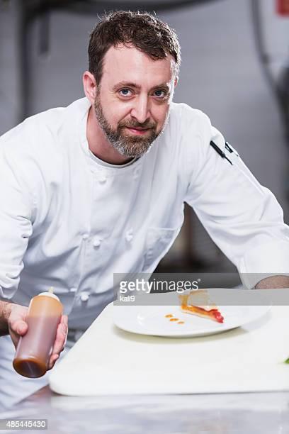 Küchenchef in restaurant, bereitet vor dessert-Platte