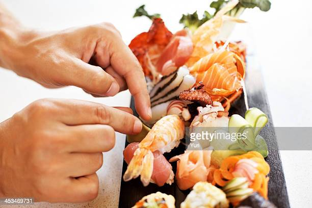 Chef in action preparing a sushi dish