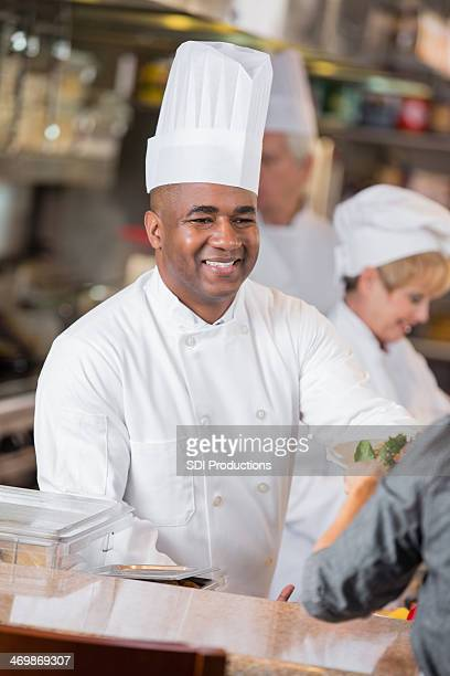 Chef in commercial kitchen delivering food to restaurant waitress