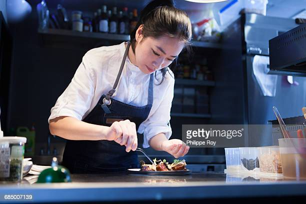 chef in commercial kitchen seasoning food - chef stock pictures, royalty-free photos & images
