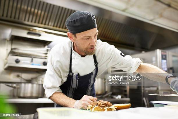 chef in kitchen near stove - chef stock pictures, royalty-free photos & images