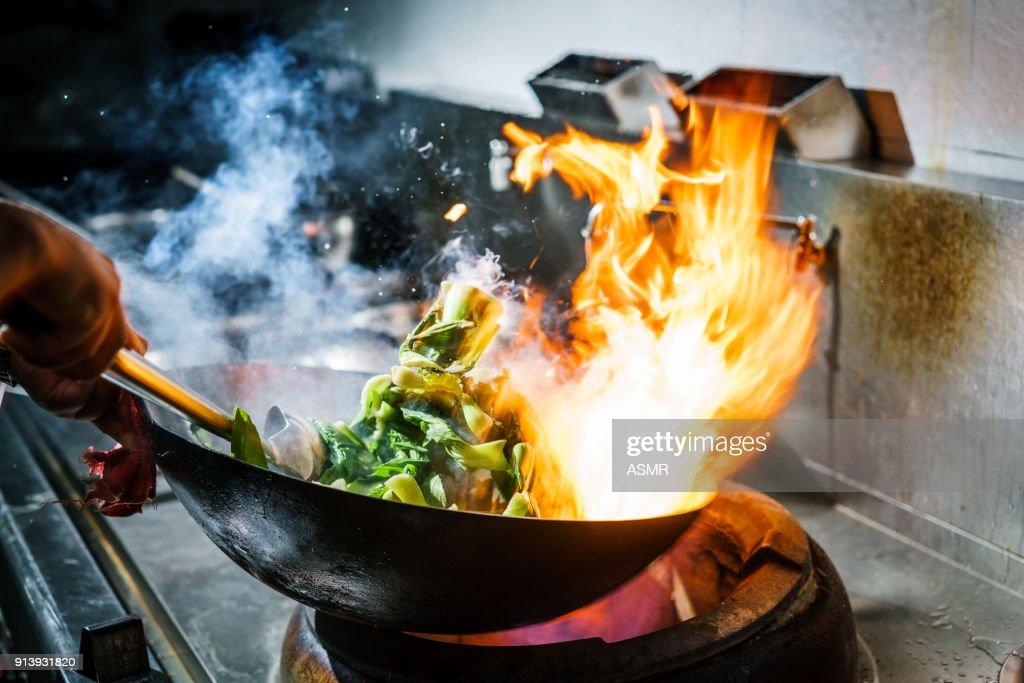Kock i restaurangkök på spis med hög brinnande lågor : Bildbanksbilder