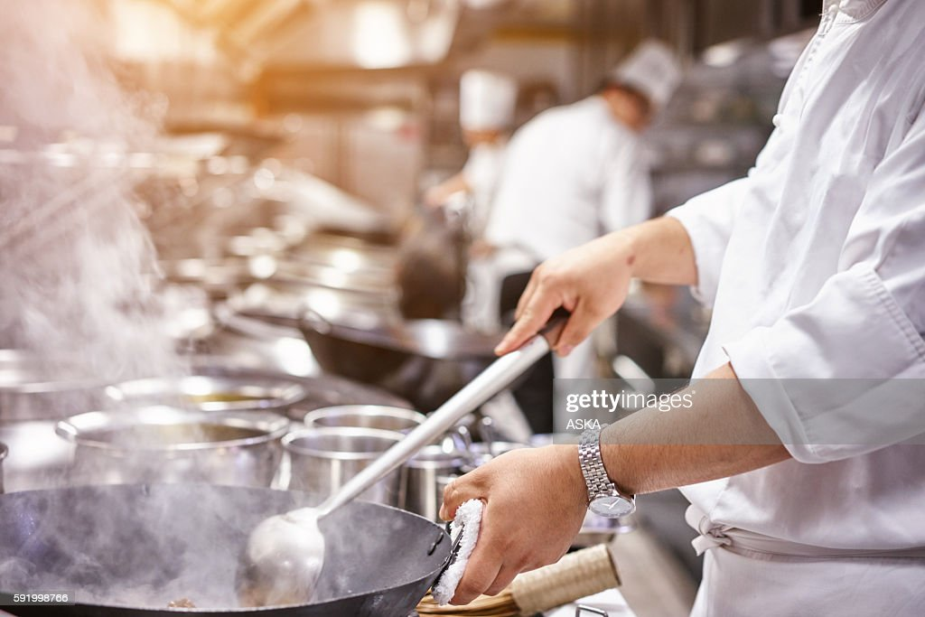 Chef in restaurant kitchen at stove with pan : Stock Photo