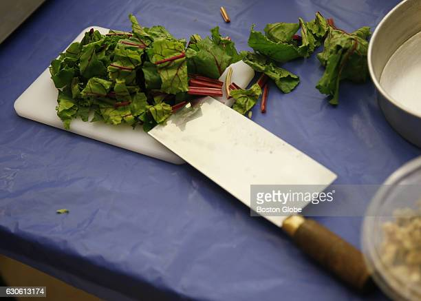 Chef Irene Li of Mei Mei Kitchen chops beet greens as she demonstrates a dish while teaching a cooking class at the Brookline Senior Center in...