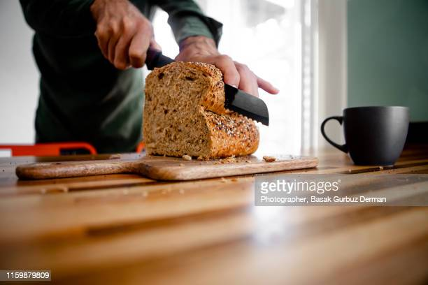 a chef is cutting a loaf of bread into slices - gluten free bread stock pictures, royalty-free photos & images
