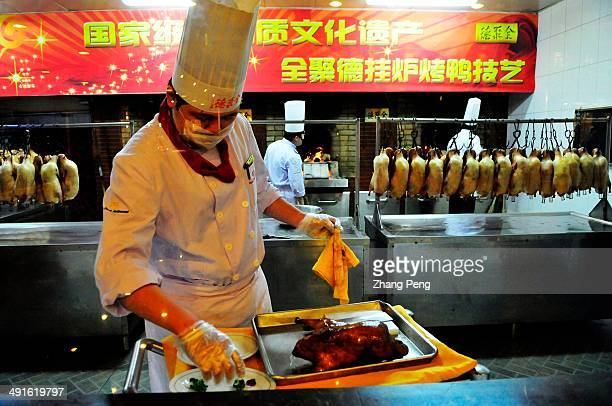 Chef is cutting roasted duck into pieces in Quanjude Roast Duck Restaurant Beijing Roast Duck is a famous China's tastiest dish with grilled stuffed...