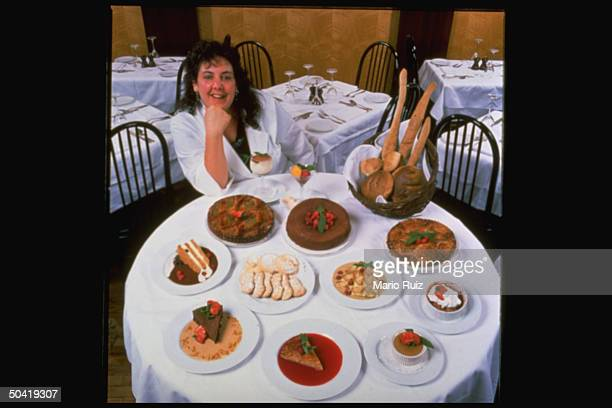 Chef Joan Winters posed sitting at a round table w various ItalianAmerican deserts on it at the Duane Park Cafe