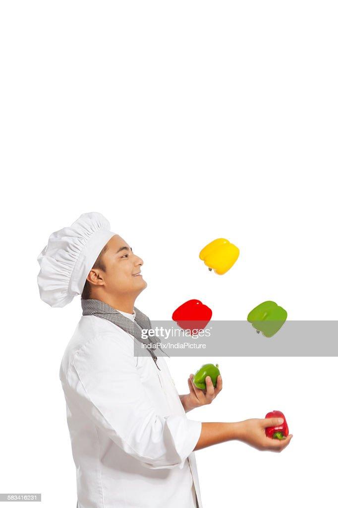 Chef juggling capsicum : Stock Photo