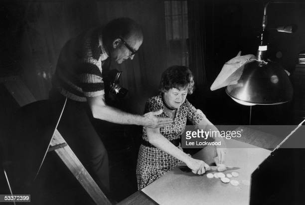 Chef Julia Child chopping squash as her husband Paul photographs her for an upcoming cookbook