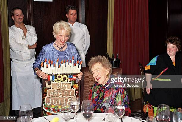 Chef Julia Child is presented with a card designed by gallery owner Nancy Thomas during a charity prebirthday dinner at the Fifth Floor restaurant on...