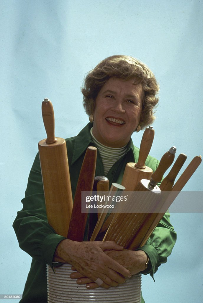 Chef Julia Child posing w. assorted rolling pins.