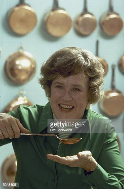 Chef Julia Child posing w spoon about to sample broth