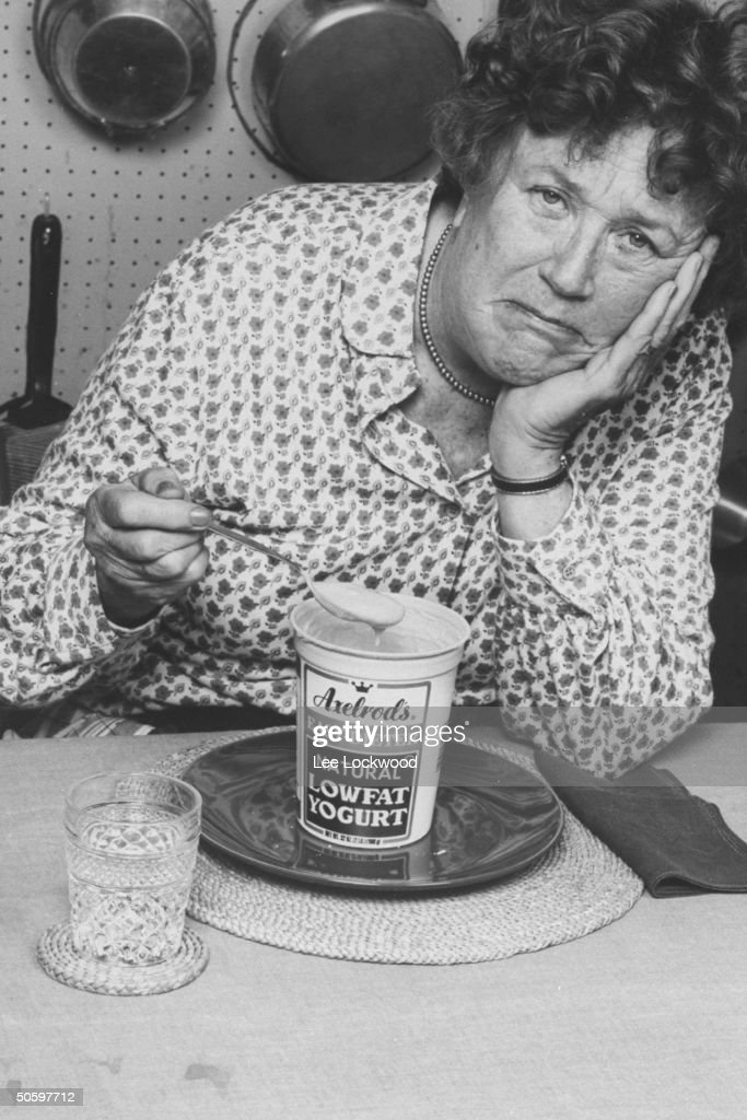 TV chef Julia Child w. a very bored expression on her face as she holds a dripping spoonful of diet yogurt from a pint container of Axelrod's Easy-Dieter Lowfat Yogurt which sits on kitchen table before her.