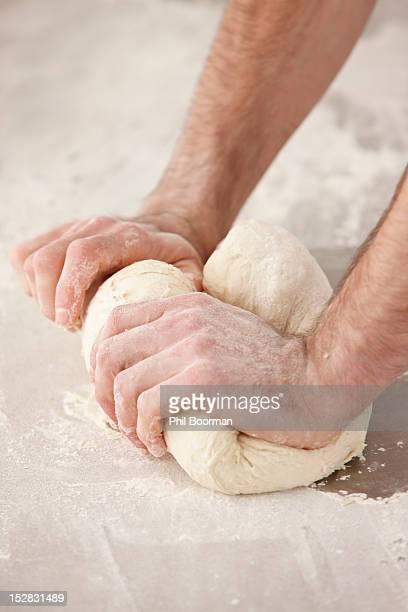 Chef kneading dough in kitchen