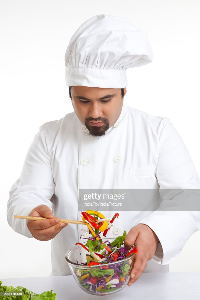 Chef looking at vegetables in bowl : Stock Photo